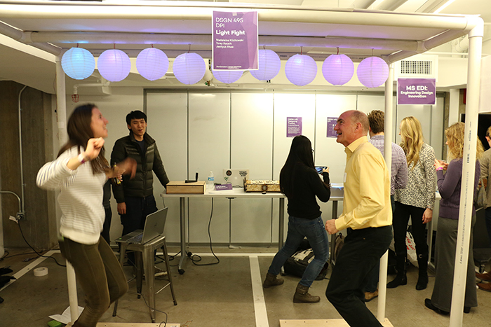 EDI student Phoebe Evans and EDI Director Ed Colgate try out an interactive lantern game designed by Segal students Torey Kocsik, Madeleine Klichowski and Jaehyuk Rhee.