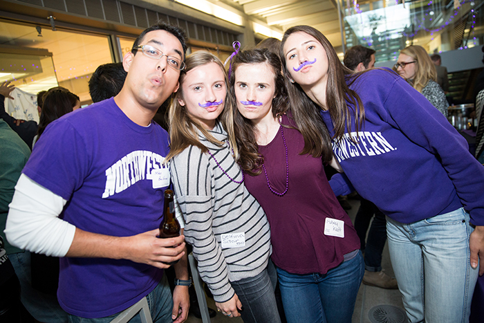 EDI Professor Mike Beltran poses with EDI students Delfina Sitar, Aubrey Kraft and Ellie Pearlman who are rocking their purple mustaches.