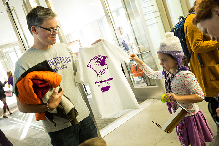 Segal Professor Ken Gentry takes a look at the t-shirt his daughter designed.